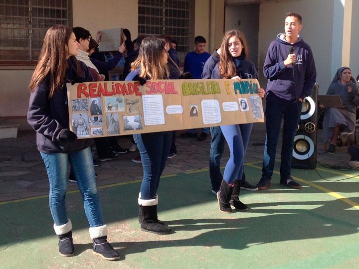 Alunos do Ensino Médio em uma apresentação de trabalho escolar no pátio da escola
